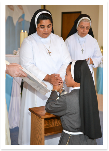 Picture of a Sister blessing another sister while she kneels and prays